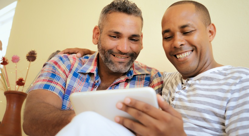 two men on a couch looking at an electronic pad